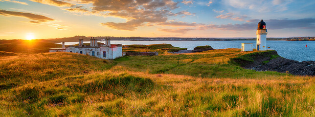 Wall Mural - Panoramic view of sunset over the lighthouse and coastguard cottages at Arnish Point