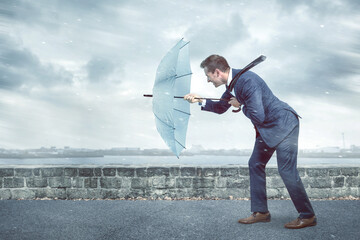 Businessman with an umbrella is facing strong headwind