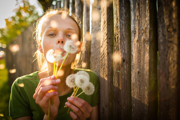 Portrait of happy young woman relaxing on a lovely summer day,  playing with dandelions