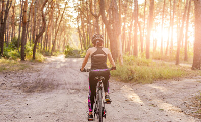 Girl riding bicycle along forest road