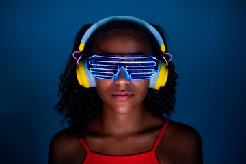 Young woman wearing headphones and futuristic led glasses on blue background - Isolated black woman wearing 3d smart glasses and headphones
