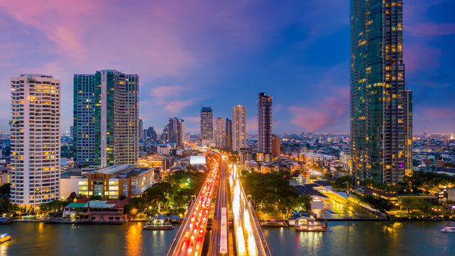 Aerial view of Taksin Bridge with Chao Phraya River, Bangkok Downtown, Thailand, Financial district and business center skylind and skyscaper urban city and high-rise buildings at night.