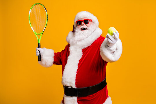 Portrait of his he nice attractive cheerful cheery glad fat overweight Santa enjoying playing badminton physical activity isolated over bright vivid shine vibrant yellow color background
