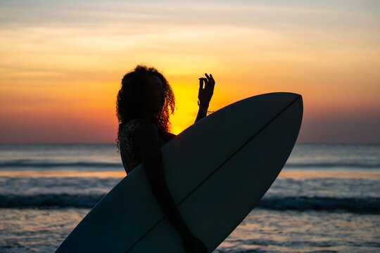 Portrait of woman surfer with beautiful body on the beach with surfboard at colorful sunset