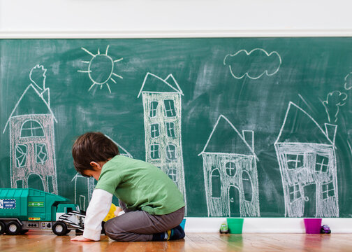 boy plays in front of chalkboard city