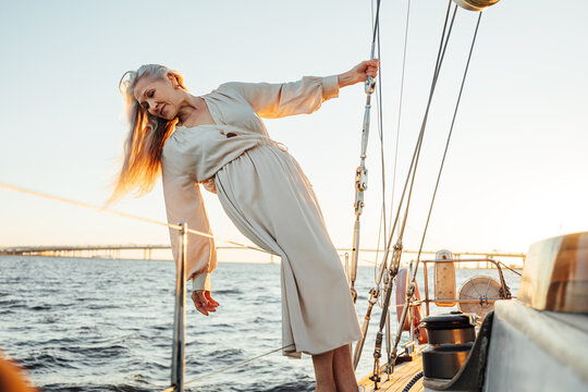 Beautiful senior woman with long hair posing on yacht and looking on water