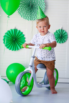 A little boy with a cap on his head sits behind a balance bike against the background of green balloons. Birthday for children. Celebrating St. Patrick's Day. Gift bike for kid