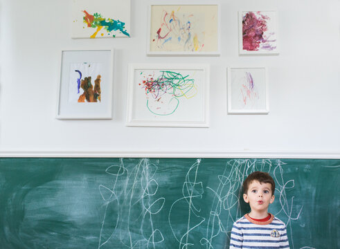 boy stands in front of scribbles on chalkboard