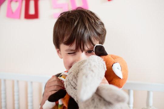 boy winks behind stuffed animal