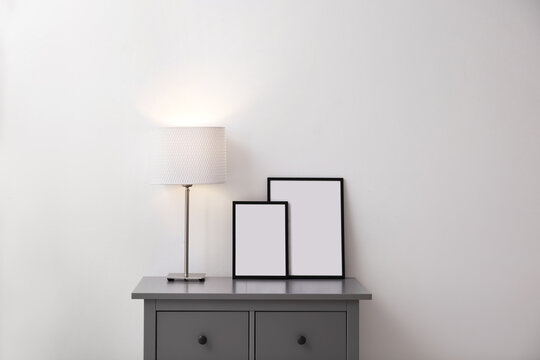 Blank poster and photo frame on cabinet near white brick wall in room. Mockup for design