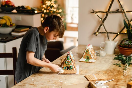 boy building and decorating a gingerbread house