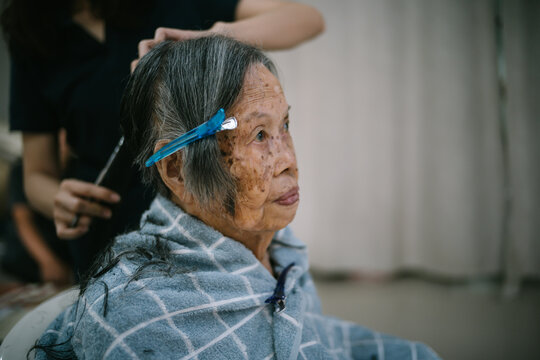 Closeup portrait of old elderly Asain woman having a haircut at home. Elderly people stay at home during the coronavirus pandemic, Self hair care during quarantine.