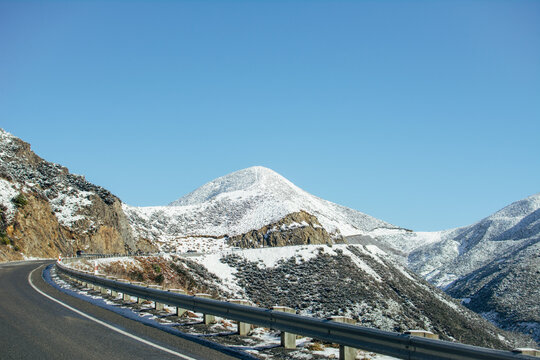 Windy road in snow covered mountains