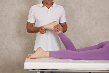 Physiotherapist massaging achilles tendon of female paitient. Ankle injury rehabilitation concept