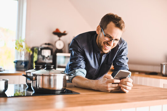 attractive nerd guy with glasses in stylish kitchen follows a recipe or  reads news on the phone