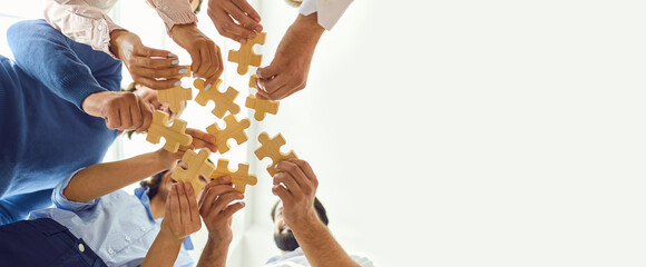 Happy company employees joining parts of jigsaw puzzle during work meeting or team building activity