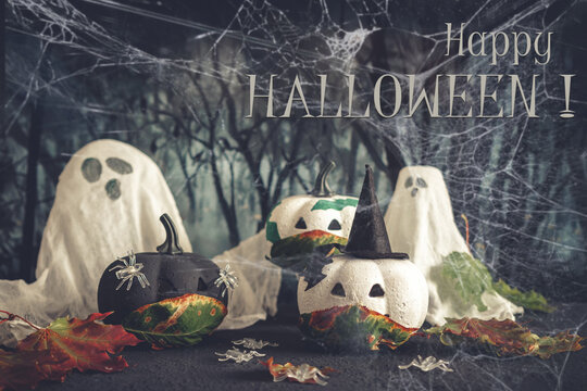 Happy halloween holiday. Halloween decorations, black and white pumpkins mask coronavirus,bats, ghosts black background. Halloween party greeting card mockup with copy space. Halloween greeting banner