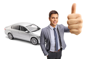 Happy young man showing a thumb up sign in front of a new silver car
