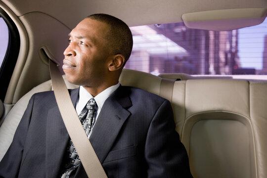 African businessman wearing seatbelt in back seat of car