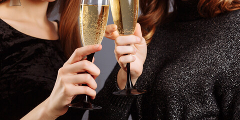 Beautiful glasses of champagne in women's hands. Ladies Look and smile into the camera, isolated on gray background