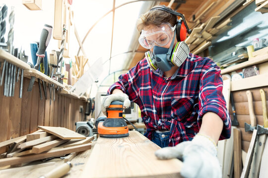 Young adult caucasian mid aged professional female carpenter grinding raw wood with orbital sander tool in carpentry diy workshop. Feminine women equality concept. Women do male hobby at workbench