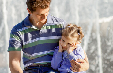 dad hugs little daughter against background of fountains on sunny day