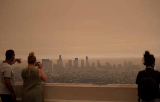 People watch as thick smoke from the Bobcat fire moves through Los Angeles