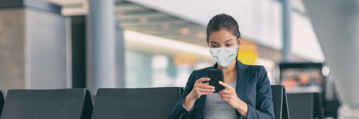Mandatory face wear to cover mouth with mask protection. Asian woman using mobile phone app waiting flight departure in airport terminal banner. Panoramic crop of travel tourist during coronavirus.