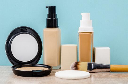 Liquid fluid foundation glass bottle on makeup sponges and brush makeup.
