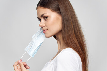 woman puts on mask on face side view white t-shirt