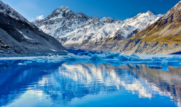 Hooker glacier melting with snow capped Mount Cook in the distance reflecting in the lake and a beautiful clear blue sky