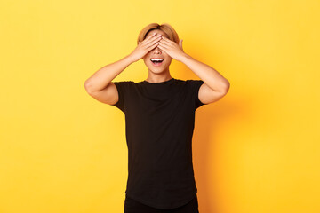 Portrait of amused and excited smiling blond guy shut eyes with palms, waiting for surprise,...