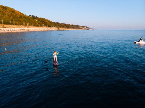 Attractive Woman on Stand Up Paddle Board, Woman paddling on sup board and enjoying turquoise transparent water. Tropical travel, wanderlust and water activity concept. Sunset and relax