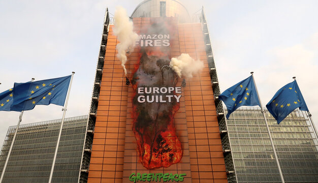 Greenpeace activists take part in an action outside the European Union headquarters