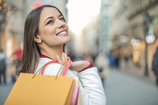 Portrait of beautiful young woman smiling with shopping bags