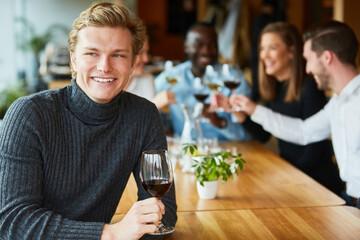 Glücklicher junger Mann mit einem Glas Rotwein