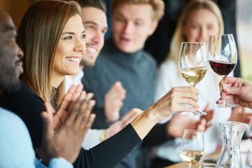 Junge Frau beim Anstoßen mit einem Glas Wein
