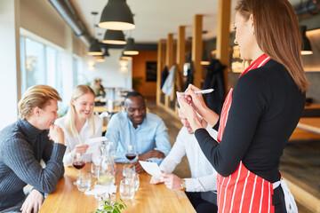 Kellnerin wartet auf die Bestellung der Gäste