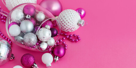 Christmas baubles in a wine glass on a pink background