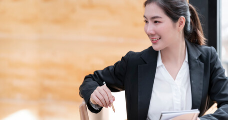 Portrait of young asian businesswoman holding pencil and notebook while sitting in modern office.