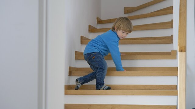 Blond hair child learn to go go down stairs, develop new skills home