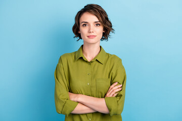 Photo of charming lady short hairstyle calm serious self-assured look confident folded hands camera wear green shirt isolated blue color background