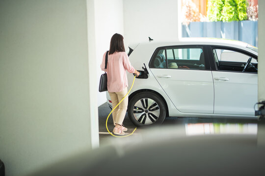 Woman charging a electric car at a garage