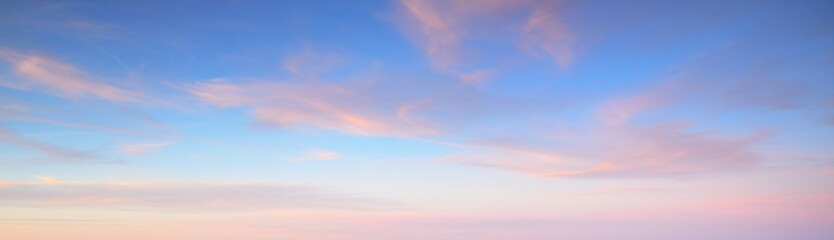 Clear blue sky with glowing pink cirrus and cumulus clouds after storm at sunset. Dramatic...