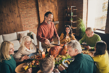 Photo of full family eight people gathering sit bearded father hold knife cut turkey talk laugh funny joke drink wine eat served dinner big table generation in evening living room indoors