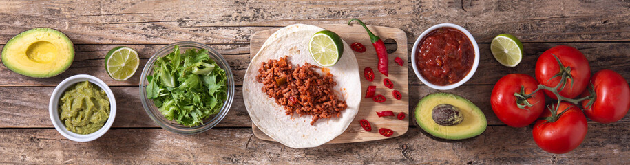 Mexican tacos ingredients on wooden table. Panorama view