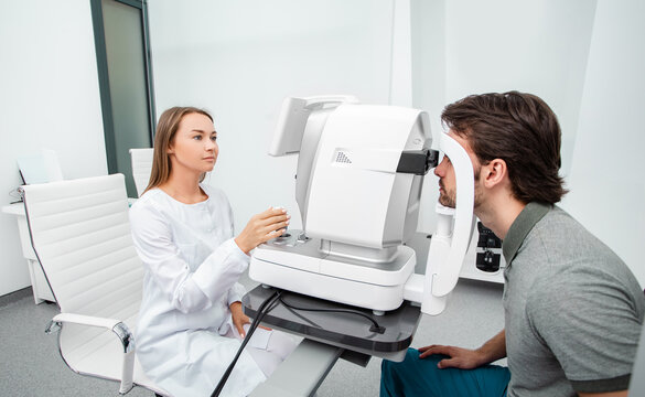 Optometrist using autorefractor check patient vision. Eye exam of adult people