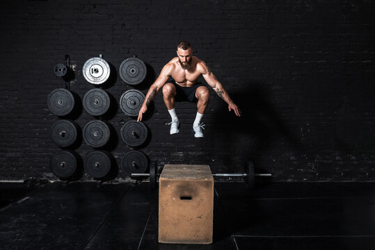 Young strong fit sweaty muscular man with big muscles doing box jump workout in the gym as hardcore cross training