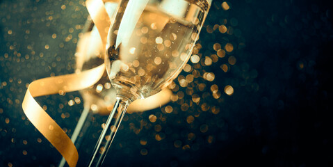 Two champagne glasses with golden ribbon and gold glitter splash bokeh on dark background. Luxury...