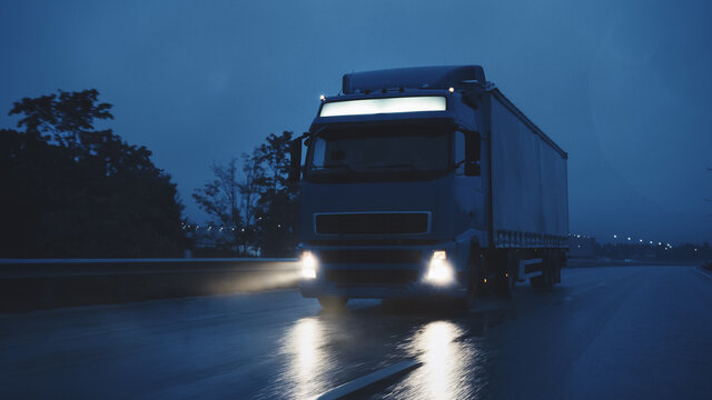 Long Haul Semi-Truck with Cargo Trailer Full of Goods Travels At Night on the Freeway Road, Driving Across Continent Through Rain, Fog, Snow. Industrial Warehouses Area. Front Shot